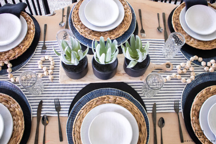 Navy and Black tablescape filled with layered table linens and pops of greenery.