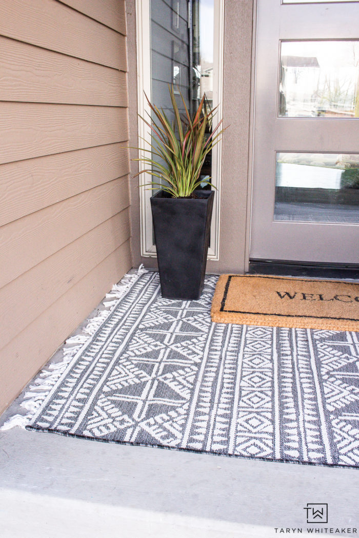 Neutral spring porch decor with layered black and white outdoor rugs and black planters.