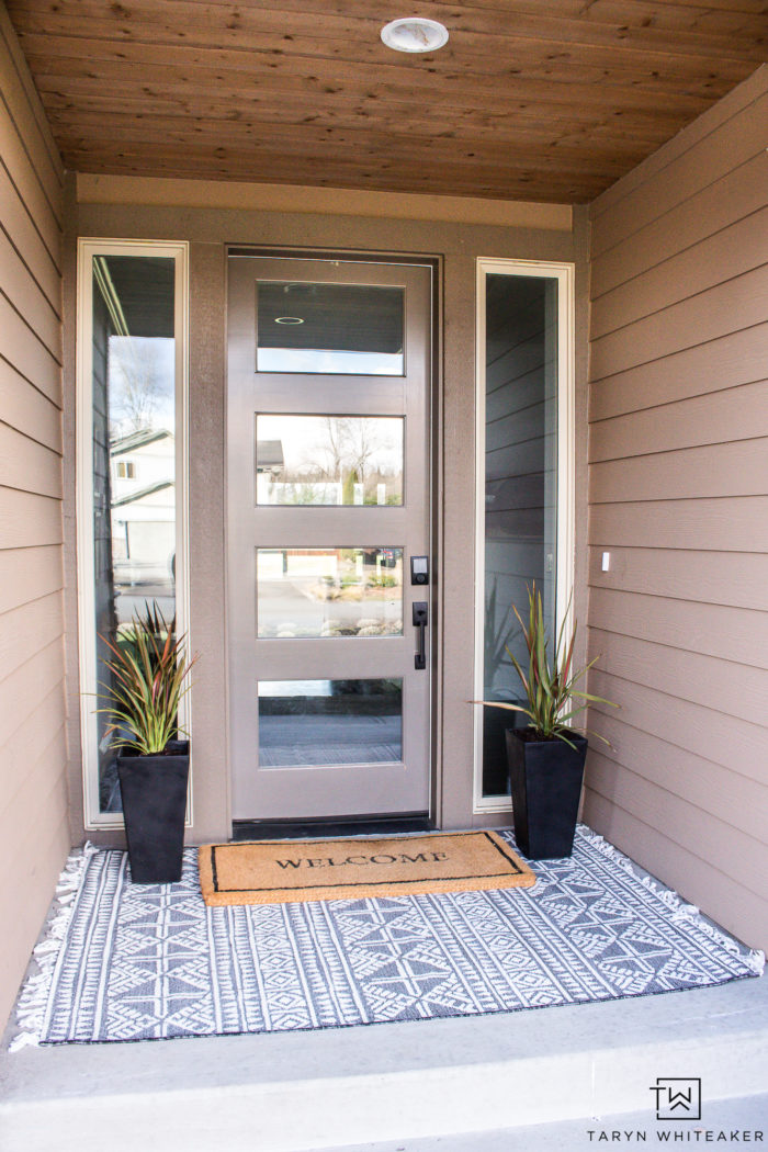 Neutral modern spring porch decor with layered black and white outdoor rugs and black planters.