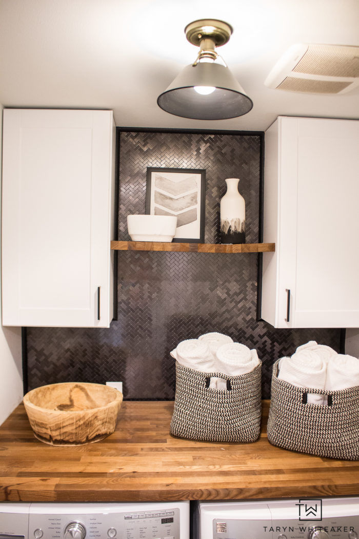 Tour this Rustic Modern Laundry Room that you can easily DIY yourself! From pre-made cabinets, butcher block countertops and peel and stick tile backsplash!