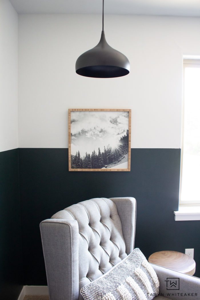 Modern cozy reading corner with green color blocked walls and modern black chandelier with mountain print.