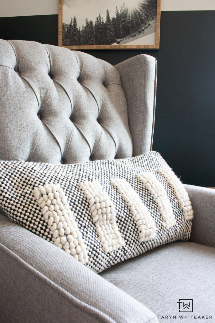 Light gray tufted recliner with cozy neutral throw pillow.