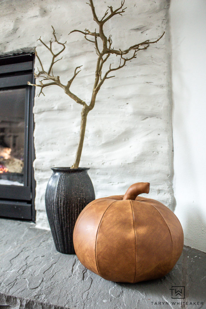 Create your own Minimalistic Halloween Mantel Decor with these simple ideas of a cascading bat display, branches and a few pumpkins!