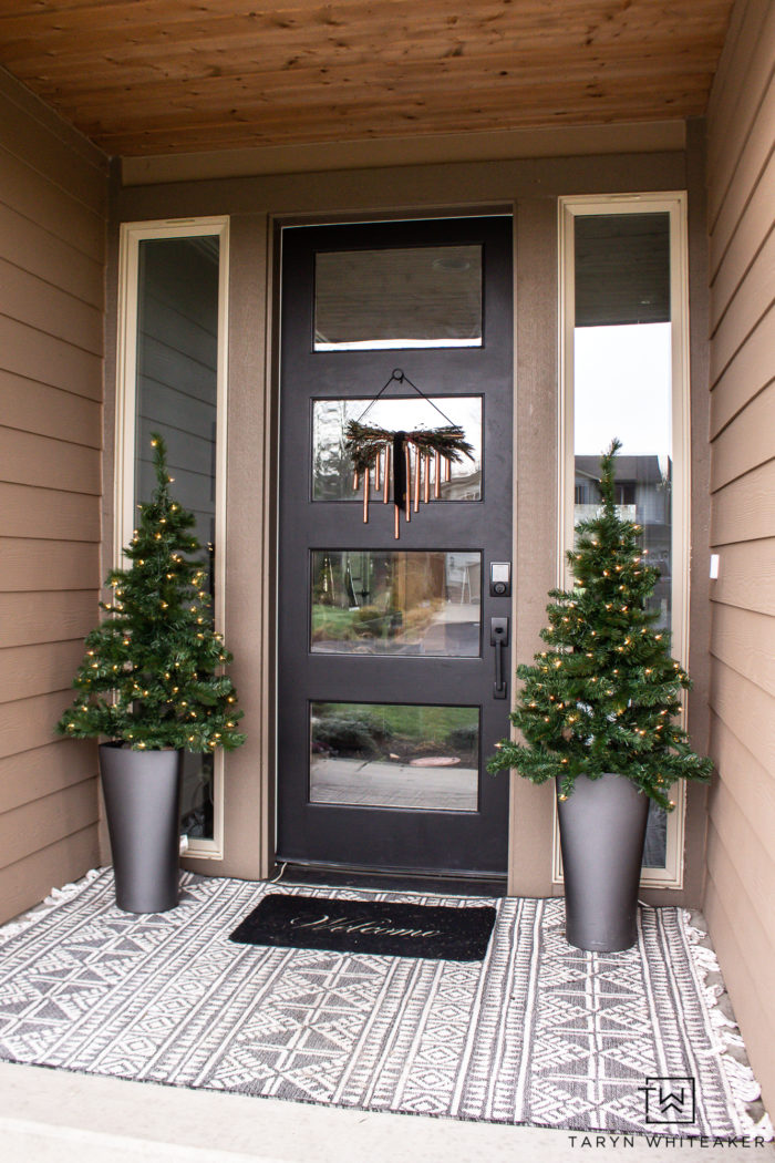 Simple Christmas porch using mini Christmas Trees and a DIY copper door decor piece.