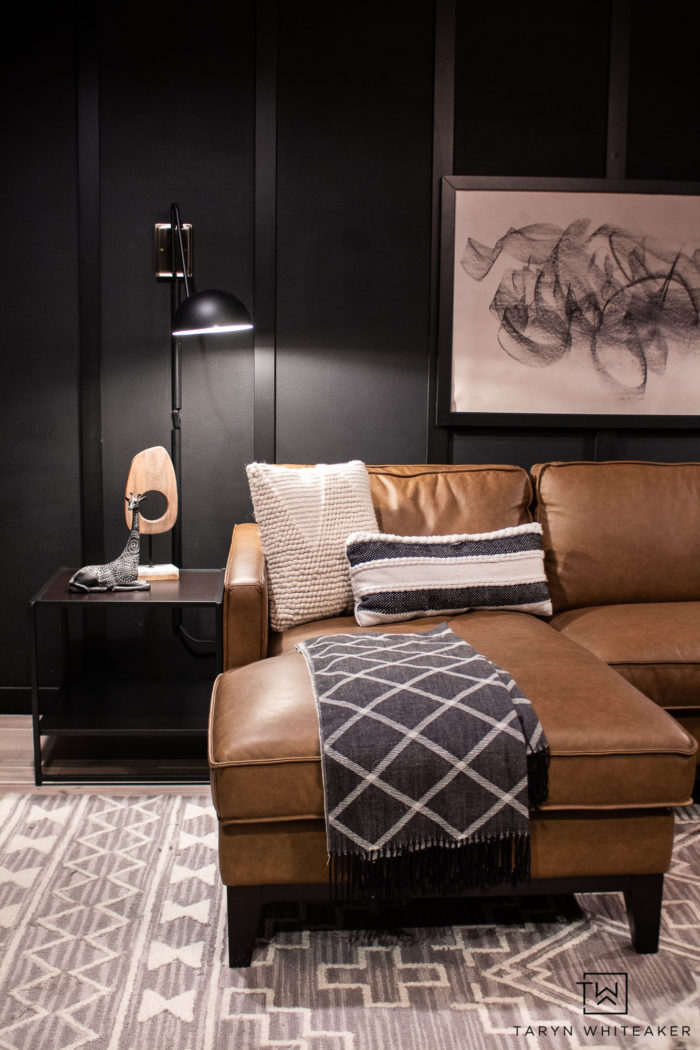 Classic mid century modern den space with dark black walls and trim and cognac leather sofa.
