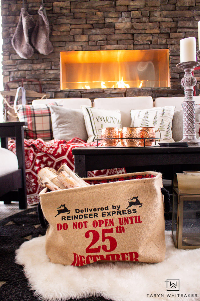 Tour this Christmas outdoor fireplace all decorated for the holidays with a cabin chic vibe! It's all about trees, pillows and staying cozy!
