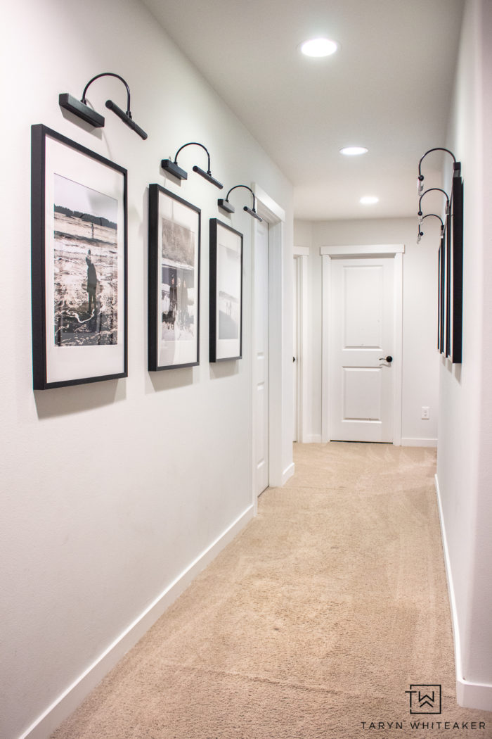 Spruce up your boring hallway with this Black and White Hallway Gallery Wall using personal pictures and wireless sconces!