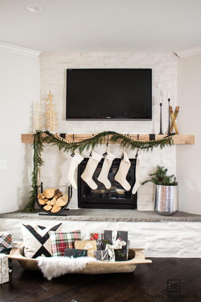 Scandinavian style Christmas mantel using cedar garland, wood beads and modern accents.