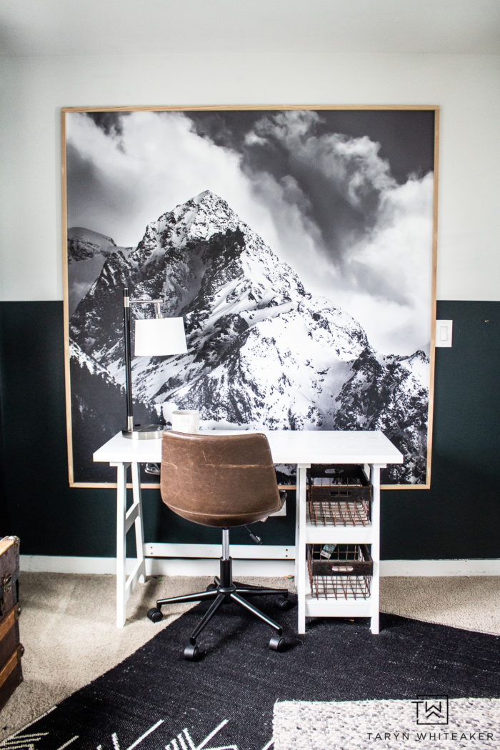 Bedroom desk space with large mountain print and white modern desk.