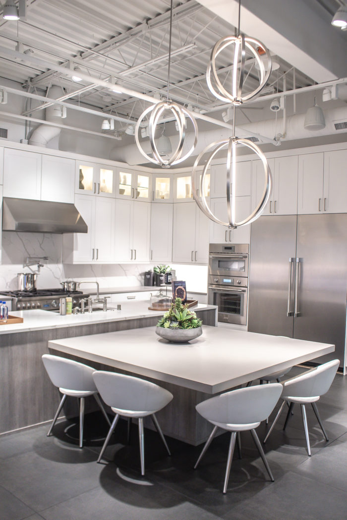All white kitchen with industrial lighting and grey wood accents.