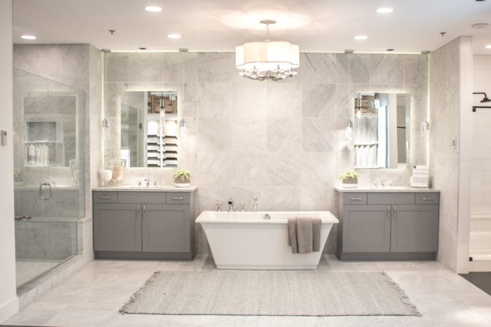 Cottage style primary bathroom with double vanities, large floating tub and solid wall tile.
