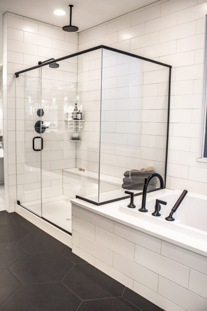 Black and White farmhouse Bathroom with black hexagon flooring and large white subway tile
