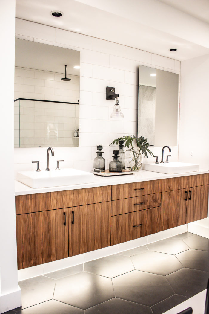 mid century modern bathroom with black flooring and white subway tile, with floating wood vanity.