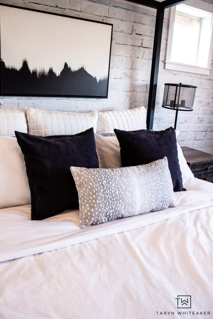 Black and white bedroom decor with antelope accent pillow and rustic touches.