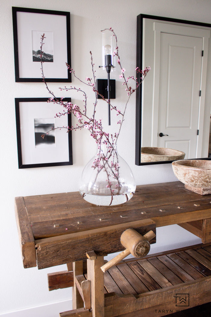 Modern spring entry decor that includes black and white decor and pops of pink with fresh spring branches in a vase.