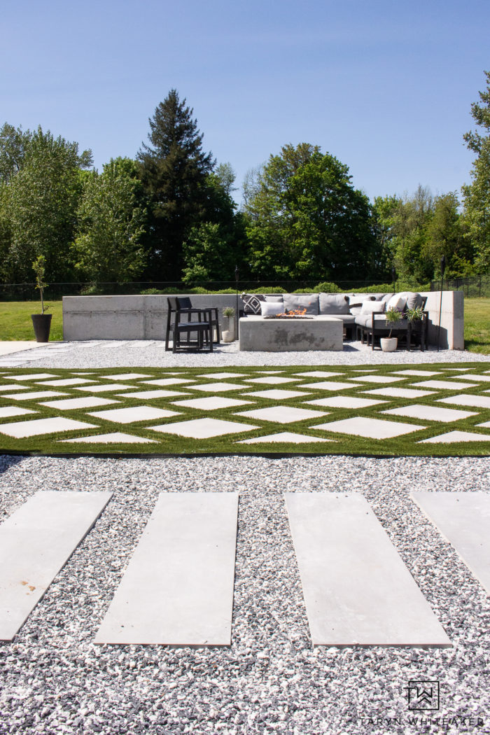 Backyard landscape design with concrete fire pit and modern outdoor space complete with grid style turf.
