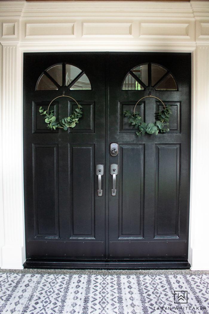 black front door with minimalistic eucalyptus wreaths