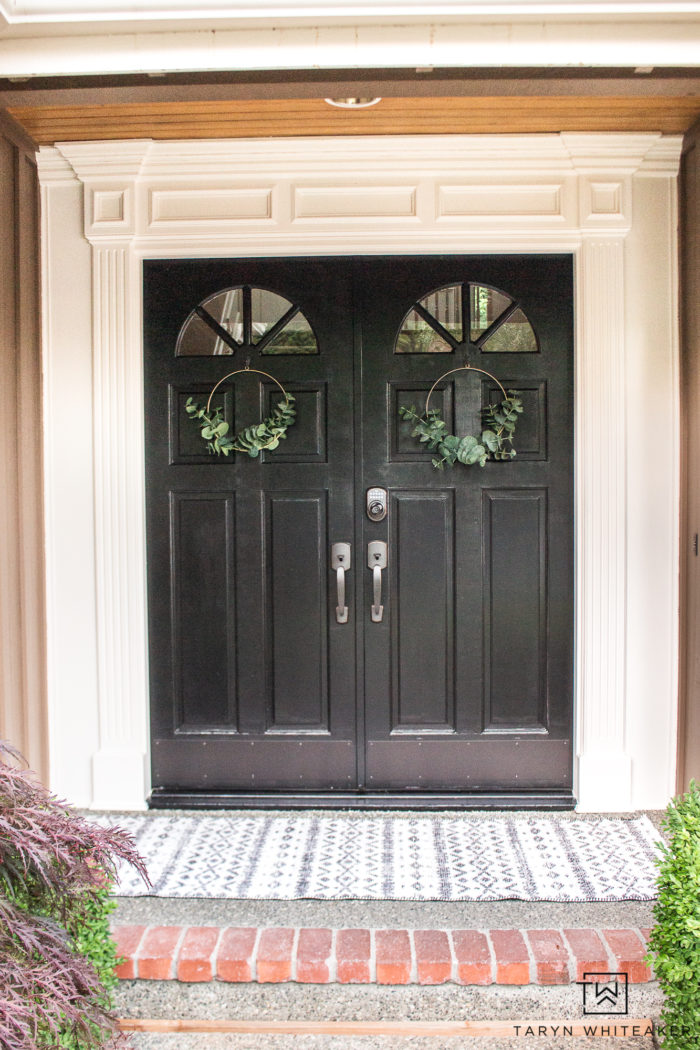 Black front door with white trim and farmhouse accents
