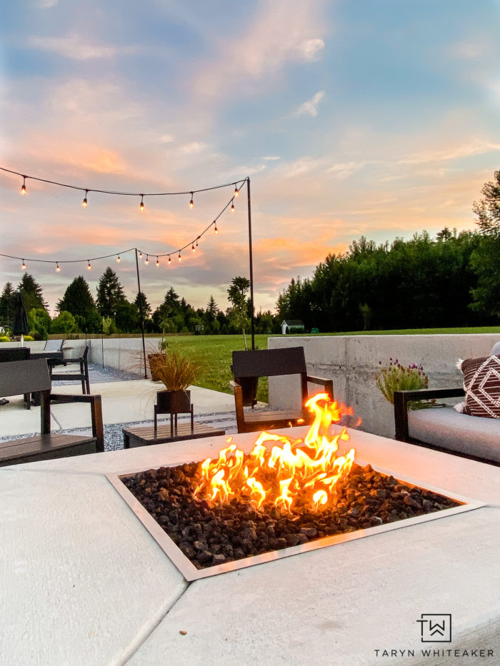square concrete firepit with modern patio decor and hanging string lights