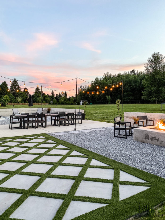 modern backyard design with diagonal turf and pavers with large outdoor table and modern square firepit