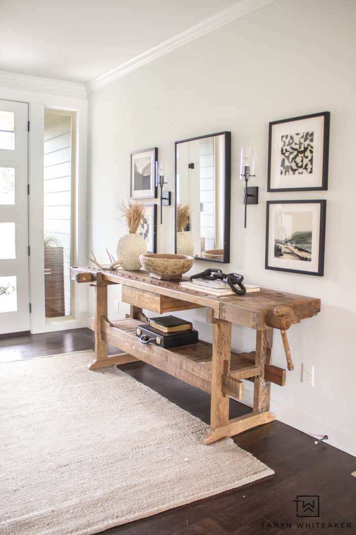 Rustic Modern entry way with vintage carpenters table console and fine art prints