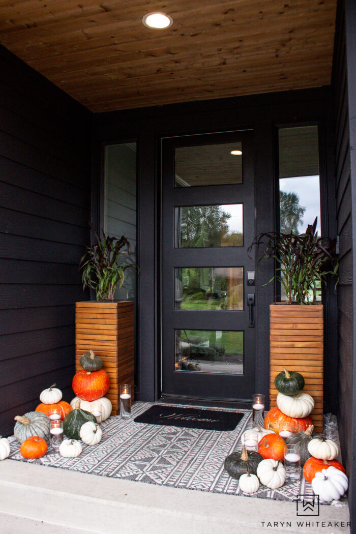 Modern fall porch display with dark exterior and heirloom pumpkins